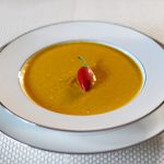 Golden Turmeric Vegetable Soup With Cashews and Curry Spices.